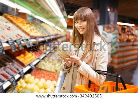 Woman choosing fruits at big supermarket  - stock photo