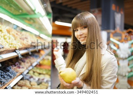 Woman choosing fruits at supermarket and holding quince - stock photo