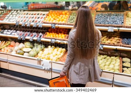 Woman choosing fruits at supermarket. Back view. - stock photo