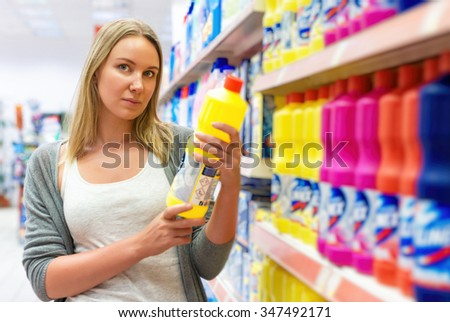 Woman choosing household chemicals in the store. - stock photo
