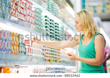 woman choosing produces in dairy shopping mall - stock photo