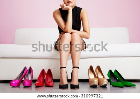 Woman choosing shoes or trouble with high heels. Sitting on the white sofa. Shopping.  - stock photo