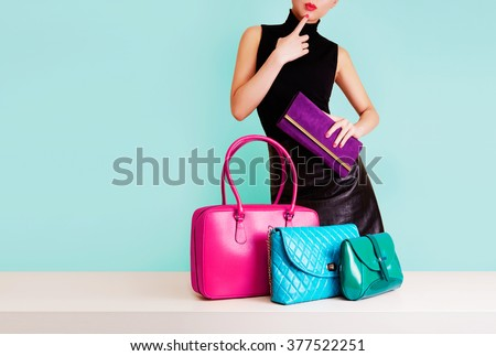 Woman choosing the bag from many colorful bags.Isolated on light blue background. Shopping addiction.