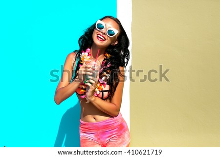 Woman choosing the bag from many colorful bags.Isolated on light blue background.Shopping addiction.Beautiful girl with long wavy hair.Brunette with curly hairstyle,laughing and smiling,crazy emotions - stock photo