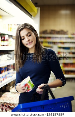 Woman choosing yogurt in supermarket - stock photo