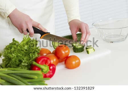 Woman chopping cucumber in a white kitchen. Prepairing salad with vegetables.