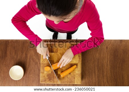 woman chopping up carrots on a wooden chopping board taken from a birds eye view from above