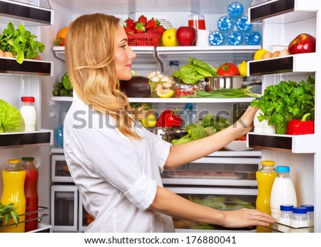 Woman chosen milk in opened refrigerator, cool new fridge full of tasty organic nutrition, female preparing to cook, healthy eating concept - stock photo