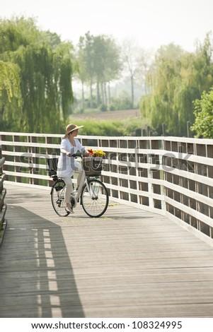 Woman ciclying on a wooden bridge - stock photo