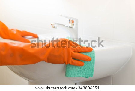 Woman clean a sink with orange gloves - stock photo