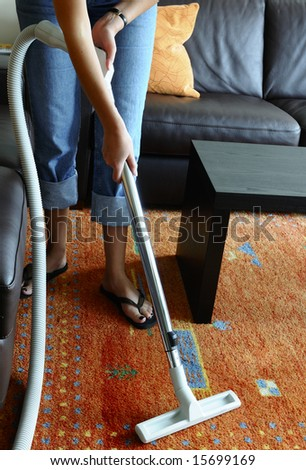 Woman cleaning a carpet with central vacuum cleaner - stock photo