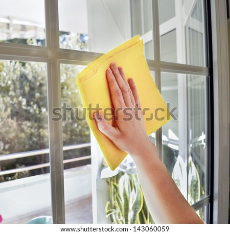 Woman cleaning a window with yellow cloth - stock photo