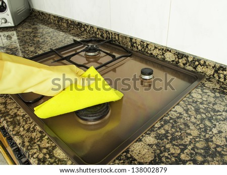woman cleaning burner in the kitchen with yellow cloth - stock photo