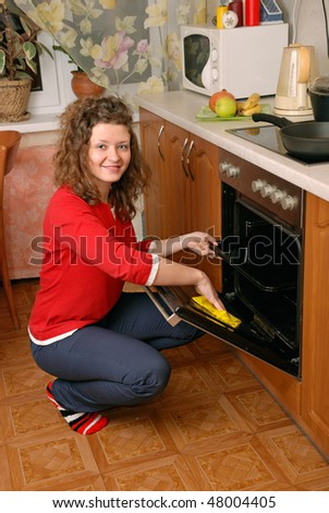 woman cleaning contemporary kitchen oven - stock photo