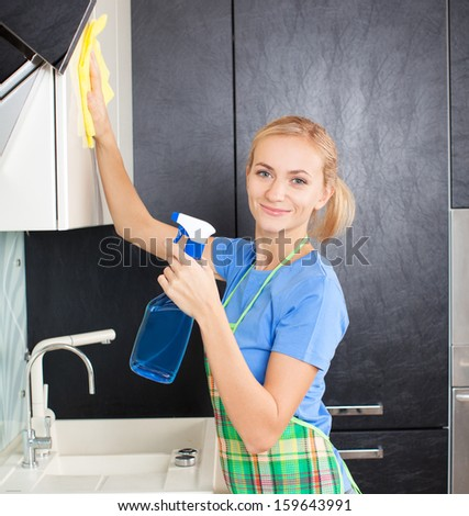 Woman cleaning cupboard. Female doing housework