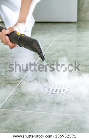 Woman cleaning  drain in bathroom with steam - stock photo