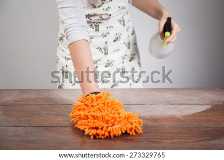 Woman cleaning dusty wooden desk with orange rag  - stock photo