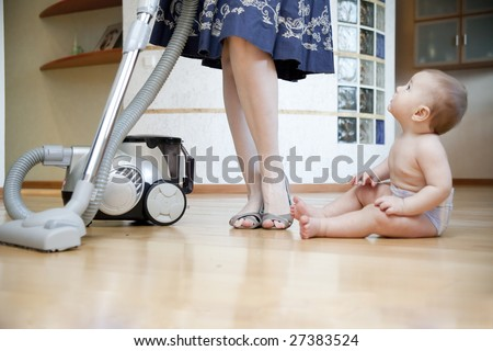 woman cleaning floor and baby sitting nearby - stock photo