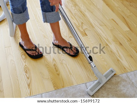 woman cleaning hardwood and tile floor with central vacuum cleaner - stock photo