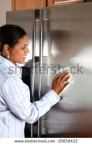 Woman cleaning her stainless steel refrigerator with a cloth - stock photo