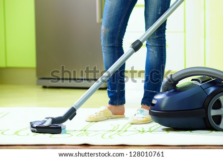 woman cleaning home with vacuum cleaner - stock photo