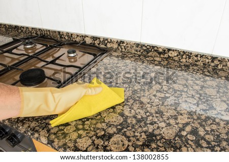 Woman cleaning kitchen with yellow cloth - stock photo