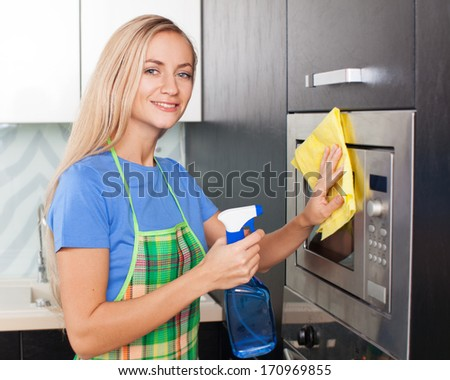 Woman cleaning microwave at kitchen. Female doing housework - stock photo