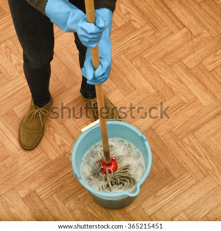 Woman cleaning parquet floor - stock photo