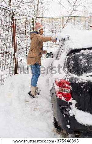 Woman cleaning snow car  in cold day of winter