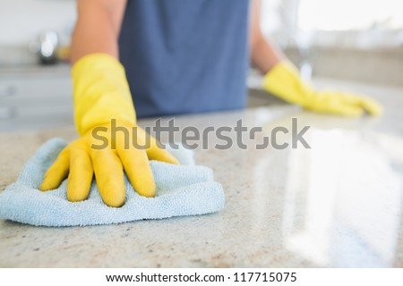 Woman cleaning the counter  in the kitchen - stock photo