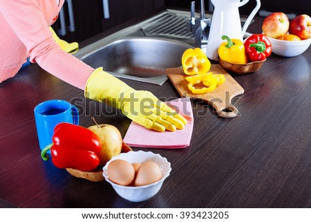woman cleaning the counter in the kitchen at home