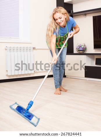 Woman cleaning the floor at home. Young housework - stock photo