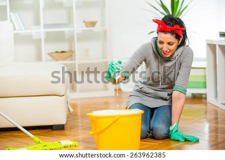 Woman cleaning the floor while kneeling at home - stock photo
