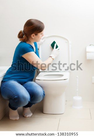 woman cleaning toilet seat with sponge  at  home - stock photo
