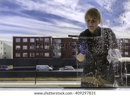 Woman cleaning windows outside, shot from inside the apartment - stock photo