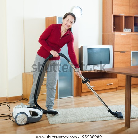 woman cleaning with vacuum cleaner on parquet floor in living room  - stock photo