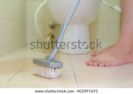 woman cleanning a bathroom toilet with  brush - stock photo