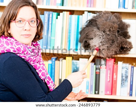 Woman cleans bookshelf with duster of peacock feathers - stock photo