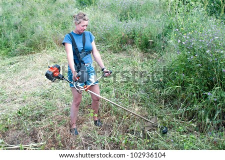 Woman clearing weeds with a strimmer