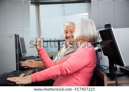 Woman Clenching Fist While Looking At Man In Computer Class