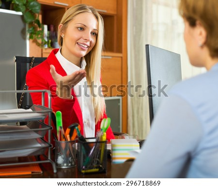 Woman clerk and client discussing possible contract indoor - stock photo