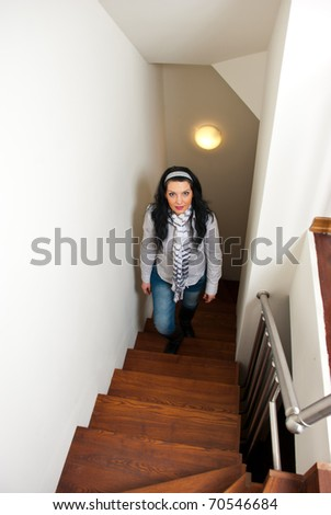 Woman climb up interior wooden  stairs in her home