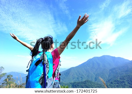 woman climber enjoy the beautiful view at mountain peak  - stock photo