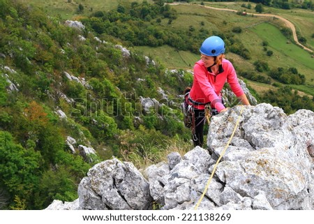 Woman climber escalate aerial limestone ridge - stock photo