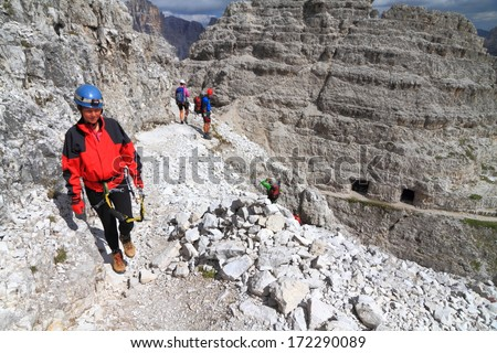 Woman climber follows a mountain trail in Dolomite Alps, Italy