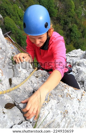 Woman climber gripping hand holds on steep limestone route - stock photo