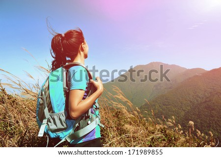 woman climber looking into the wilderness on mountain peak  - stock photo