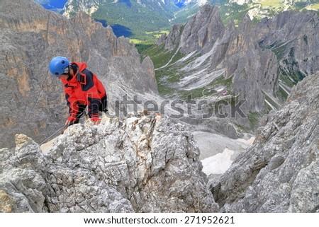 """Woman climber on aerial rock while climbing via ferrata """"Merlone"""", Cadini di Misurina, Dolomite Alps, Italy - stock photo"""