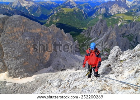 "Woman climber walking along via ferrata ""Merlone"" in Cadini di Misurina, Dolomite Alps, Italy"
