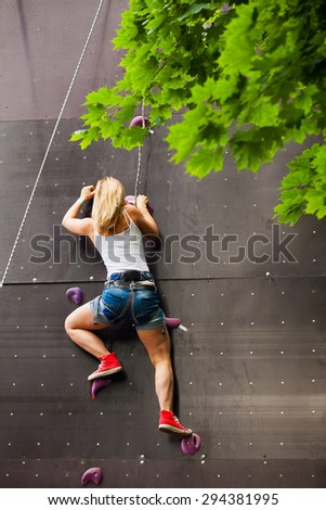 woman climbing artificial rock wall - stock photo